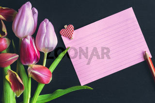 Tulips bouquet and a striped paper note