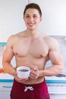 Bodybuilder junger Mann trinkt trinken Kaffee in der Küche Hochformat morgens Morgen
