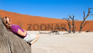 Woman leans on tree in desert surrounded. Enjoying and relaxing.
