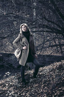Young fashion blond woman walking in autumn forest