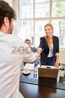Junge Geschäftsfrau begrüßt Kollegen