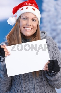 Happy girl in santa hat holding letter in hand