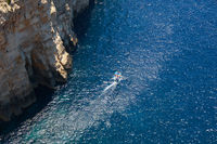 Touristic boat under steep cliff over Mediterranean sea on south part of Malta