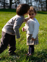 portrait of two male and female siblings, 3 and 5 years old, kissing each other on the cheek