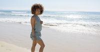 Female wearing jumpsuit walking along beach
