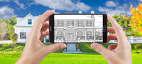 Hands Holding Smart Phone Displaying Drawing of Home Photo Behind