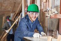 Schreiner sägt Holz an der Bandsäge