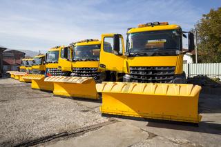 Yellow snowplow trucks in line
