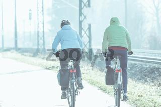 Ein Paar in dicken Jacken macht einen Ausflug mit dem Fahrrad im Winter.