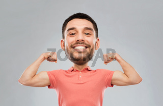 smiling man showing biceps over gray background