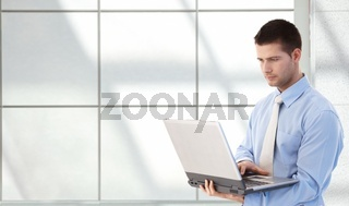 Young professional using laptop in office lobby