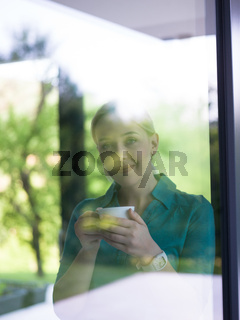 young woman drinking morning coffee by the window