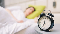 Young sleeping woman and alarm clock in bedroom at home - shallow depth of field