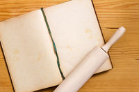 Cookbook and rolling pin on wood