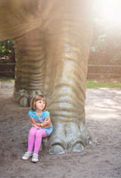 Cute little girl under huge diplodocus dinosaur