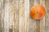red grapefruit on grunge wood
