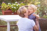 Grandmother hugs and gently kisses her grandchild in garden