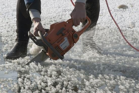 Mit der Motorsäge ein Loch in die gefrorene Wasseroberfläche schneiden zum Eistauchen