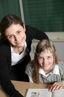 Fröhlich Lehrerin und Schülerin im Klassenzimmer mit Schulbuch