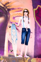 Young skateboard girl holding her longboard outdoors in front of graffiti