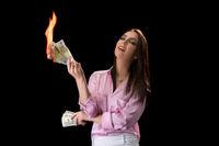 Concept of financial crisis. Woman burns money