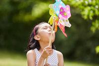 Asiatisches Mädchen spielt mit Windrad