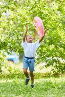 Junge läuft mit einem Schwimmring im Park