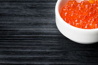 Red caviar in a cup with salt on  wooden table