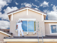 Professional House Painter Painting the Trim And Shutters of A Home.