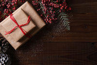 Top view of a plain brown paper Christmas present tied with red string, surrounded by pine cones and