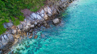 Aerial view over palm trees, rocks and sea in Phuket