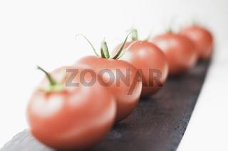 Italienische Tomate liebt Basilikum. Vorbereitung für die Vorspeise. Tomaten in Reihe