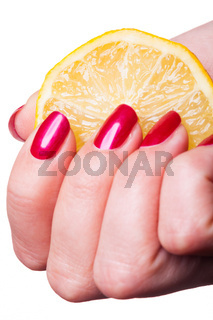 Hand with manicured nails squeeze lemon on white