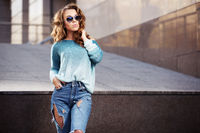 Happy young fashion woman in sunglasses on city street