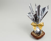 Chocolate Easter egg, silver packaging in basket. White background with copy space.