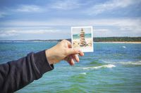 Man keeping photo on sea background