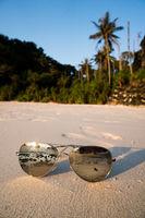 Sunglasses on sandy beach over tropical island background