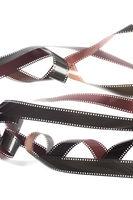 Rolls of tangled 35mm film over white