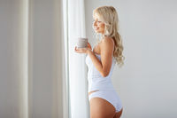 woman in underwear drinking coffee at home window