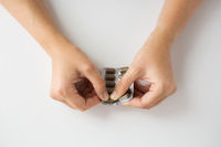 woman hands opening pack of medicine pills