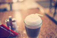 Latte coffee in glass toned in retro film color, selective focus, shallow DOF