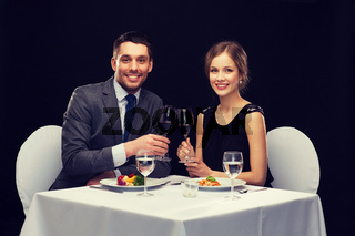 smiling couple eating main course at restaurant