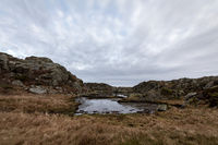 Pond by the trail in brown coastal winter landscape, at the Rovaer archipelago, Rovaer island in Haugesund, Norway.