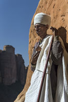Priest standing at the entry to the rock-hewn church Abuna Yemata, Gheralta, Tigray, Ethiopia