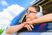 Cute girl listening to music with headphones - looking through open window of the car
