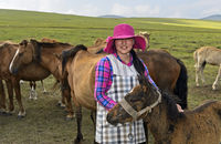 Young Mongolian woman with fashionable hat among horses, Mongolia