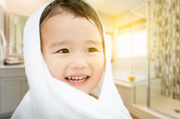 Happy Cute Mixed Race Chinese and Caucasian Boy In Bathroom Wrapped In A Towel