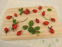 Wild fruits rose hips on wooden board