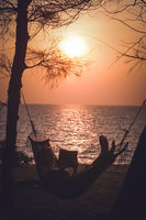 Relaxing in a hammock on a beach at sunset