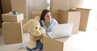 Young woman moving house with her teddy bear